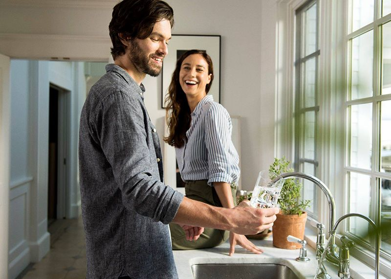 Man and Women getting water from a sink faucet