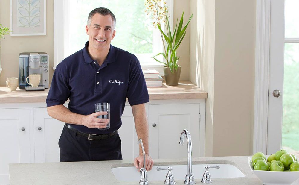 Culligan man holding cup of water near sink
