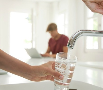 person filling drinking glass with water from tap